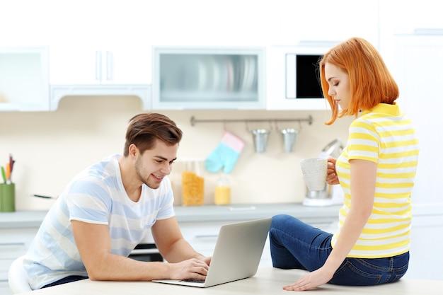Młody mężczyzna korzystający z laptopa i kobieta pijąca herbatę w kuchni