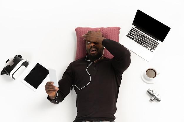 Młody mężczyzna korzystający z telefonu w otoczeniu gadżetów na białym tle