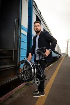 Młody mężczyzna korzystający ze składanego roweru podczas podróży pociągiem