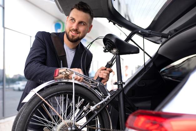 Młody mężczyzna korzystający ze składanego roweru w mieście