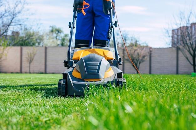 Młody mężczyzna kosi trawnik za pomocą elektrycznej kosiarki w specjalnym garniturze pracownika w pobliżu dużego wiejskiego domu na podwórku
