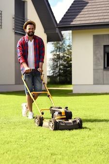 Młody mężczyzna koszący trawnik