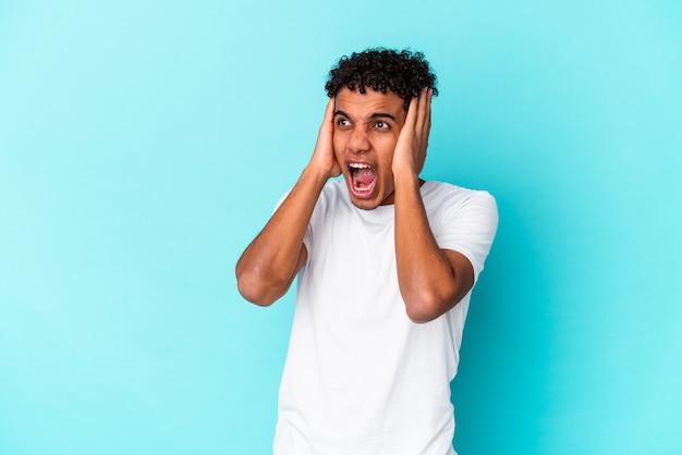 Młody mężczyzna kręcone odizolowany na niebiesko obejmujące uszy rękami, starając się nie słyszeć zbyt głośnego dźwięku