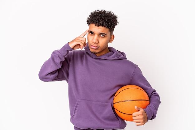 Młody mężczyzna kręcone samodzielnie grając w koszykówkę wskazując palcem świątyni, myśląc, skupiony na zadaniu