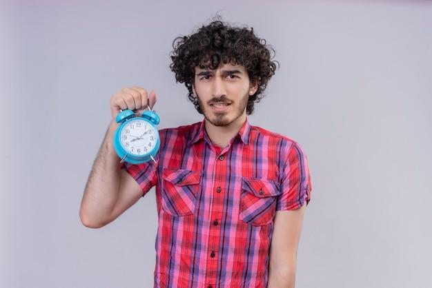Młody mężczyzna kręcone włosy na białym tle kolorowa koszula budzik