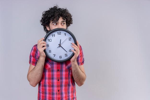 Młody mężczyzna kręcone włosy na białym tle kolorowa koszula chowając się za zegarem, odwracając