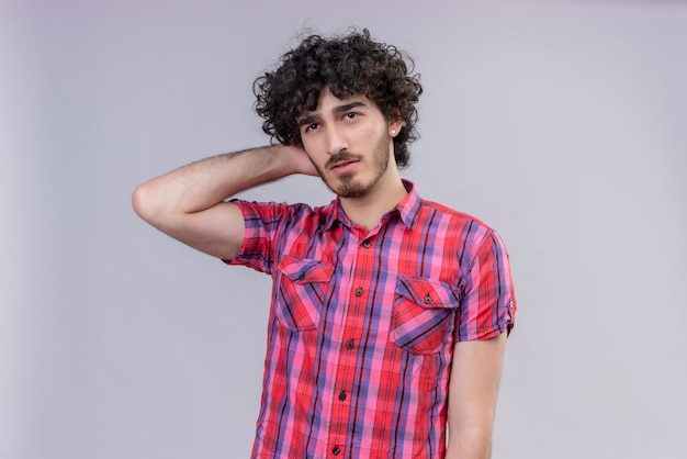 Młody mężczyzna kręcone włosy na białym tle kolorowa koszula ręka za szyją
