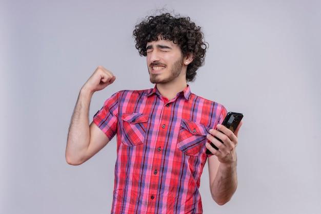 Młody mężczyzna kręcone włosy na białym tle kolorowa koszula smartfon tak pięść