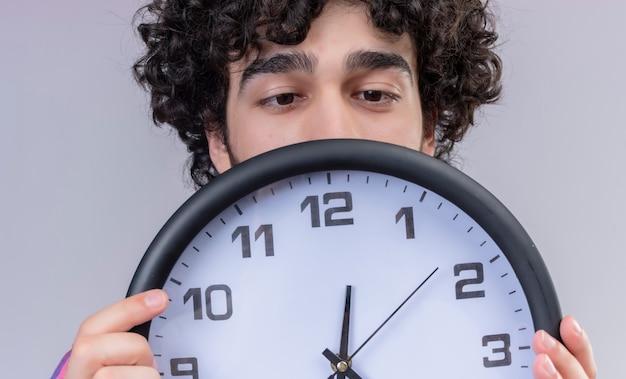 Młody mężczyzna kręcone włosy na białym tle kolorowe koszula chowając się za zbliżenie zegara