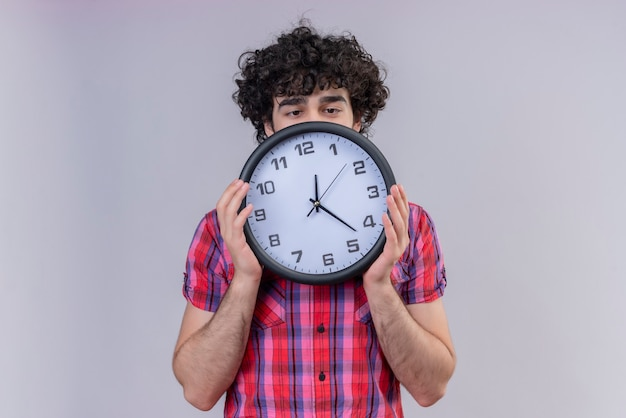 Młody mężczyzna kręcone włosy na białym tle kolorowe koszula chowając się za zegarem