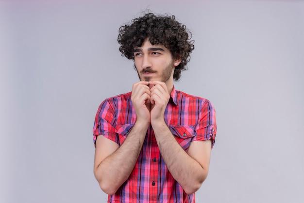 Młody mężczyzna kręcone włosy na białym tle kolorowe koszula drapanie podbródek obiema rękami