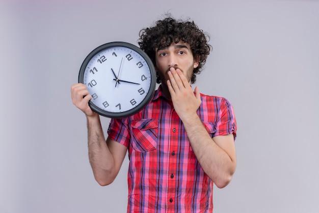 Młody mężczyzna kręcone włosy na białym tle kolorowe koszula gospodarstwa zegar zaskoczony