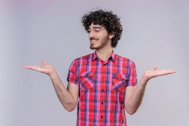 Młody mężczyzna kręcone włosy na białym tle kolorowe koszula gospodarstwa znak przedmiotu obie ręce