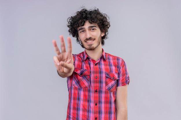 Młody mężczyzna kręcone włosy na białym tle kolorowe koszula trzy palce