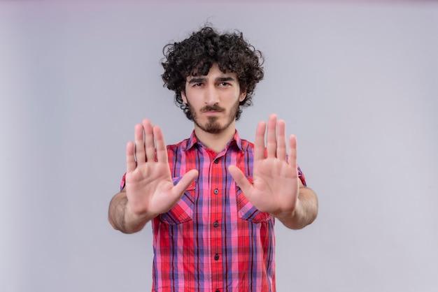 Młody mężczyzna kręcone włosy na białym tle kolorowe koszule obie dłonie do przodu