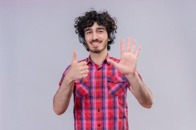 Młody mężczyzna kręcone włosy na białym tle kolorowe słuchawki koszula sześć palców