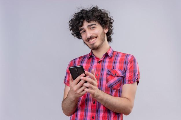 Młody mężczyzna kręcone włosy na białym tle kolorowy koszula smartphone uśmiechnięty