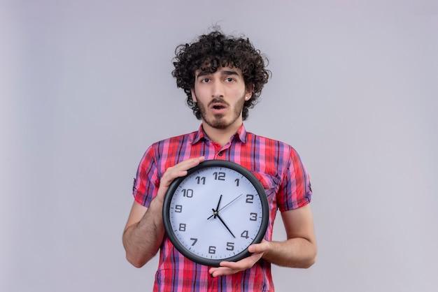 Młody mężczyzna kręcone włosy na białym tle zegar kolorowy koszula zaskoczony