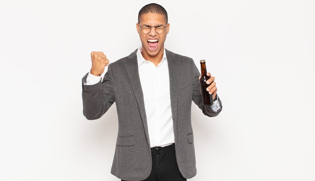 Młody mężczyzna krzyczy agresywnie z gniewnym wyrazem twarzy lub z zaciśniętymi pięściami świętując sukces