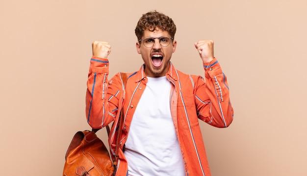 Młody mężczyzna krzyczy agresywnie z gniewnym wyrazem twarzy lub z zaciśniętymi pięściami świętuje sukces.