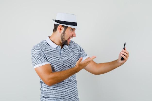 Młody mężczyzna krzyczy na rozmowę wideo w t-shirt, kapelusz i patrząc wzburzony. przedni widok.