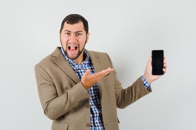 Młody mężczyzna krzyczy, pokazując telefon komórkowy w koszuli, kurtce
