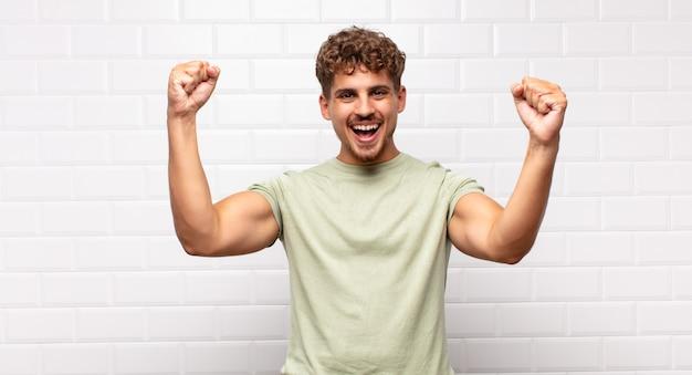Młody mężczyzna krzyczy triumfalnie, wygląda jak podekscytowany, szczęśliwy i zaskoczony zwycięzca, świętuje