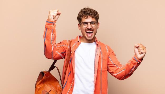 Młody mężczyzna krzyczy triumfalnie, wyglądając jak podekscytowany, szczęśliwy i zaskoczony zwycięzca, świętujący