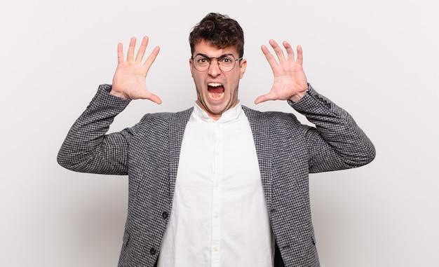 Młody mężczyzna krzyczy z podniesionymi rękami, czuje się wściekły, sfrustrowany, zestresowany i zdenerwowany