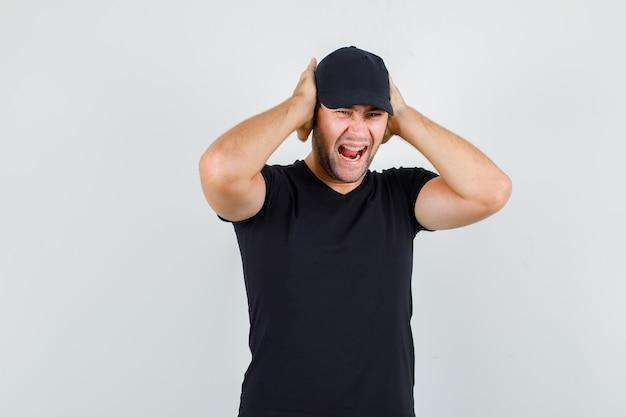 Młody mężczyzna krzyczy z rękami na uszach w czarnej koszulce