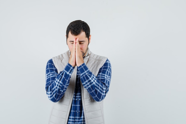 Młody mężczyzna, który marzy w koszuli, kurtce bez rękawów i wygląda na pobożnego życzenia. przedni widok. miejsce na tekst