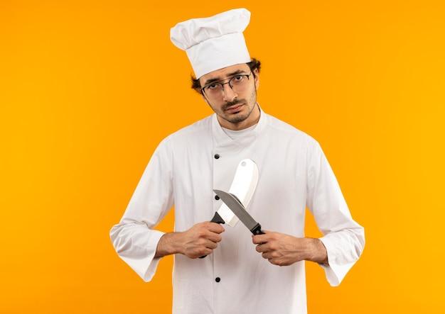 Młody mężczyzna kucharz ubrany w mundur szefa kuchni i okulary ostry tasak i nóż