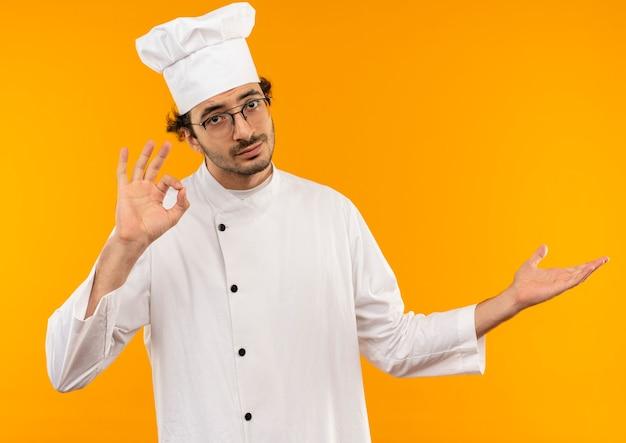 Młody mężczyzna kucharz ubrany w mundur szefa kuchni i okulary pokazujące gest okey i wskazuje ręką na bok