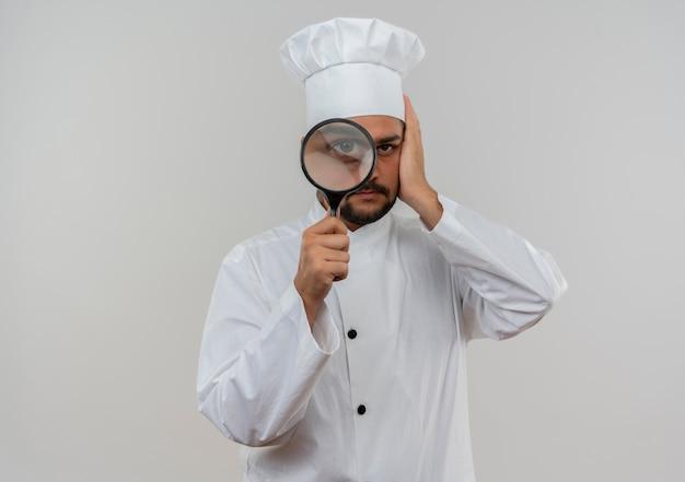 Młody mężczyzna kucharz w mundurze szefa kuchni patrząc przez lupę i kładąc rękę na głowie