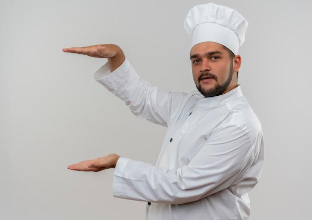 Młody mężczyzna kucharz w mundurze szefa kuchni pokazano rozmiar patrząc