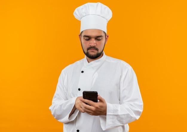 Młody mężczyzna kucharz w mundurze szefa kuchni przy użyciu telefonu komórkowego