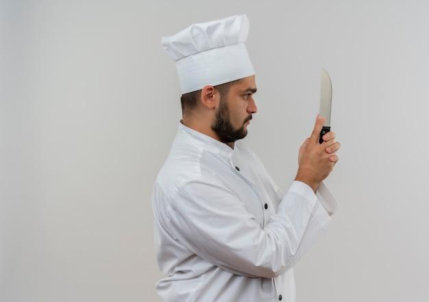 Młody mężczyzna kucharz w mundurze szefa kuchni stojącej w widoku profilu, trzymając i patrząc na nóż