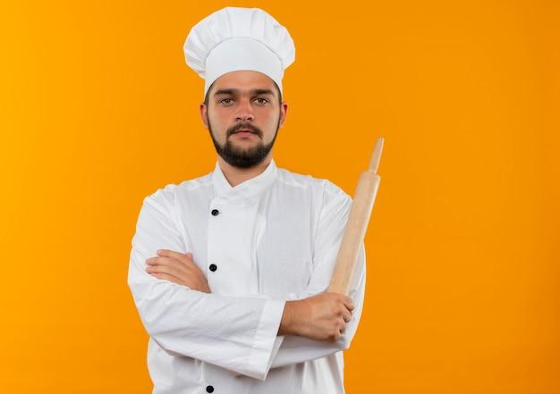 Młody mężczyzna kucharz w mundurze szefa kuchni stojącej z zamkniętą posturą i trzymając wałek do ciasta
