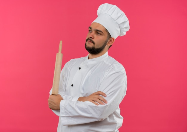 Młody mężczyzna kucharz w mundurze szefa kuchni stojący z zamkniętą postawą i trzymając wałek do ciasta, patrząc na bok