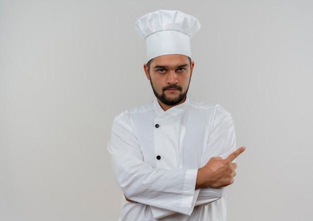 Młody mężczyzna kucharz w mundurze szefa kuchni stojący z zamkniętą postawą i wskazując na bok