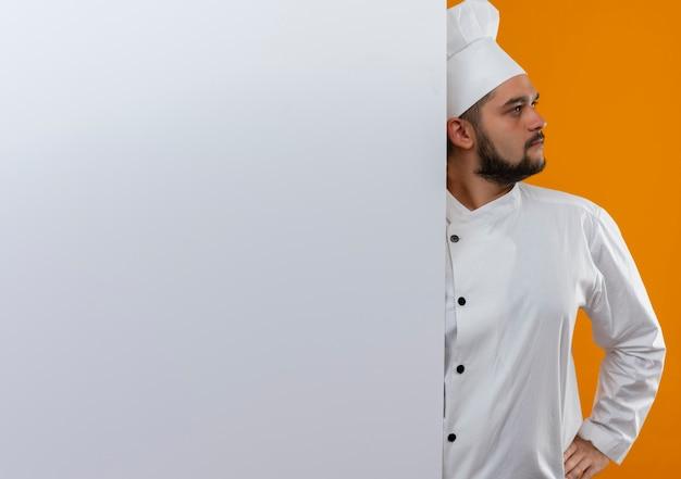 Młody mężczyzna kucharz w mundurze szefa kuchni stojący za białą ścianą, patrząc na bok, kładąc rękę na talii