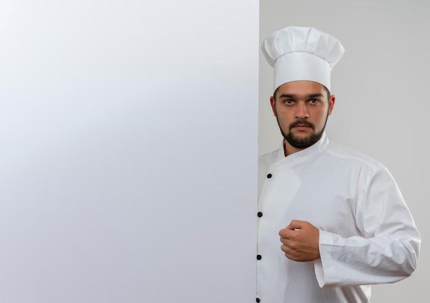 Młody mężczyzna kucharz w mundurze szefa kuchni stojący za białą ścianą patrząc