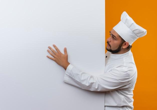 Młody mężczyzna kucharz w mundurze szefa kuchni stojący za patrząc i kładąc rękę na białej ścianie