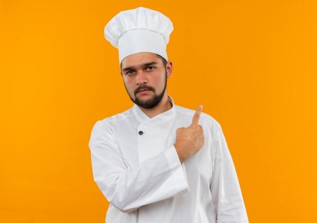 Młody mężczyzna kucharz w mundurze szefa kuchni, wskazując za patrząc