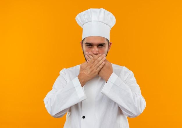 Młody mężczyzna kucharz w mundurze szefa kuchni zamykając usta rękami patrząc na białym tle na pomarańczowej przestrzeni
