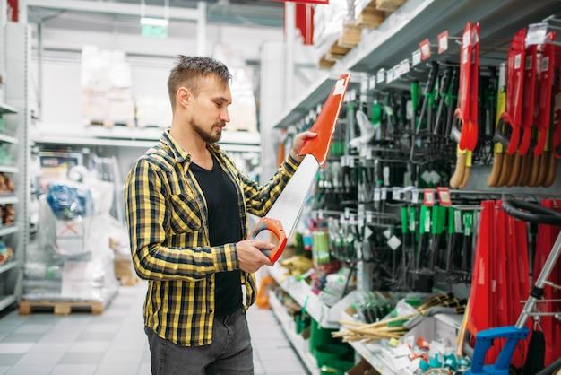 Młody mężczyzna kupujący zobaczył w supermarkecie. mężczyzna klient na zakupy w hipermarkecie, dział narzędzi