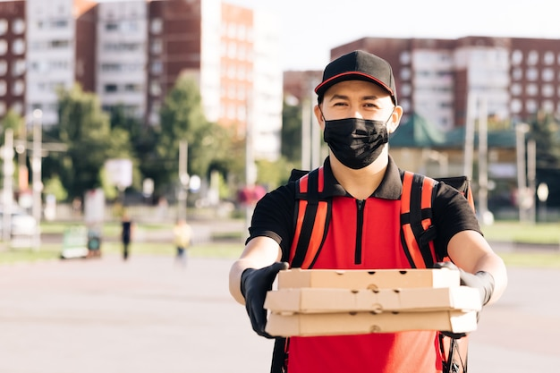 Młody mężczyzna kurier żywności noszący maskę ochronną podczas spaceru ulicą miasta z izolowaną czerwienią