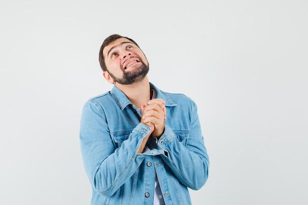Młody mężczyzna łącząc ręce w kurtce i patrząc z nadzieją