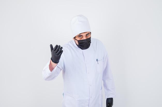 Młody mężczyzna lekarz podnosząc rękę w przesłuchaniu stanowią w białym mundurze i wygląda poważnie. przedni widok.