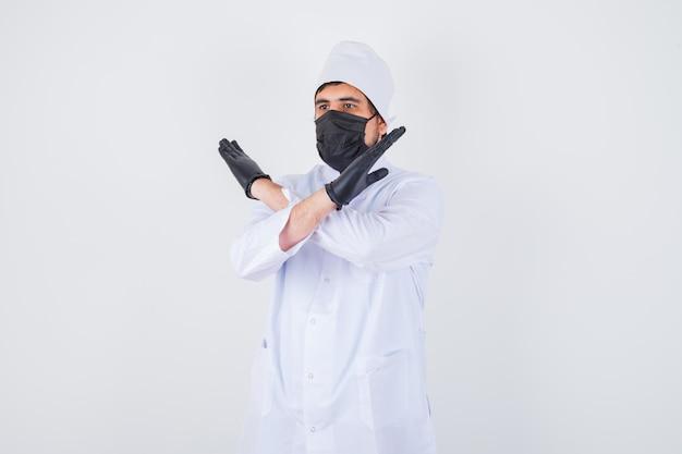 Młody mężczyzna lekarz pokazując gest stop w białym mundurze i wyglądający pewnie. przedni widok.